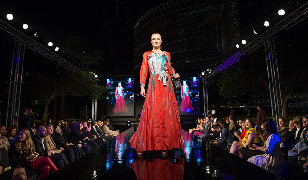 Une jeune mannequin avec une robe rouge pendant un défilée de lancement de produit