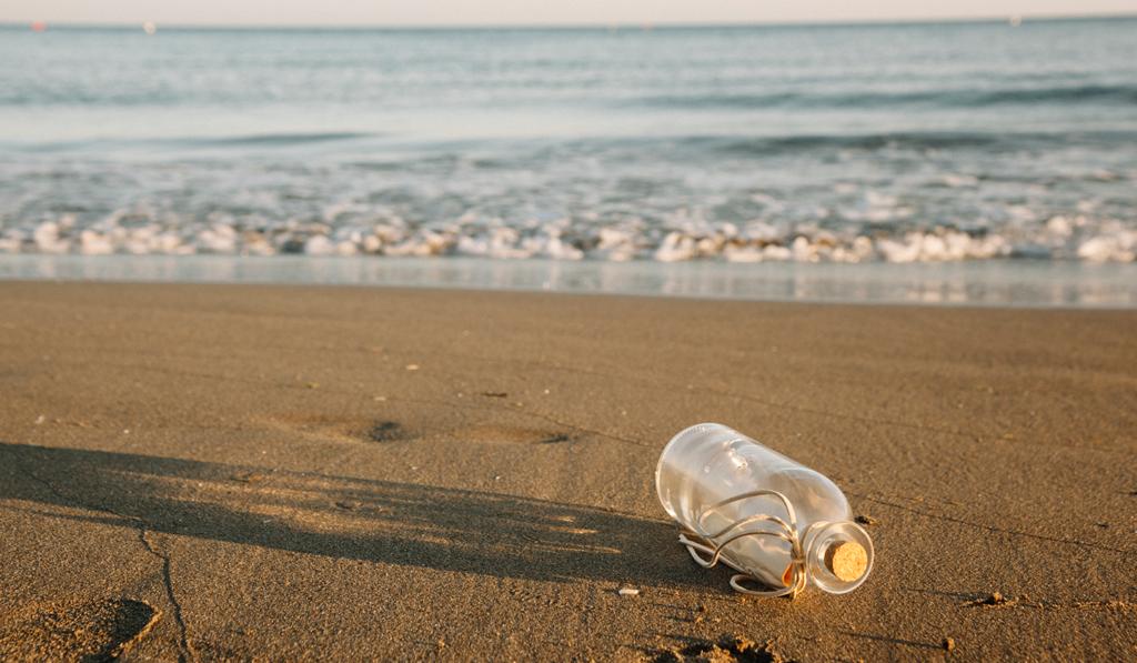 Bouteille vide avec un message sur une plage bretonne pour organiser un stage de survie d'entreprise