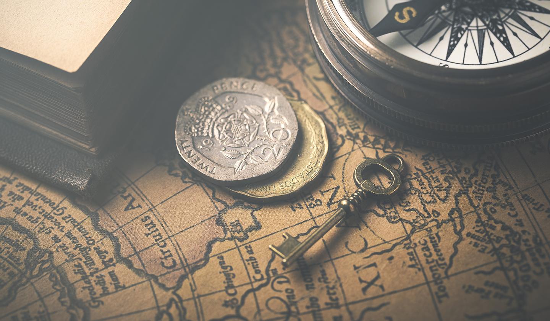 Une table de pirate avec une carte, une boussole et une clé pour organiser une chasse aux trésors d'entreprise