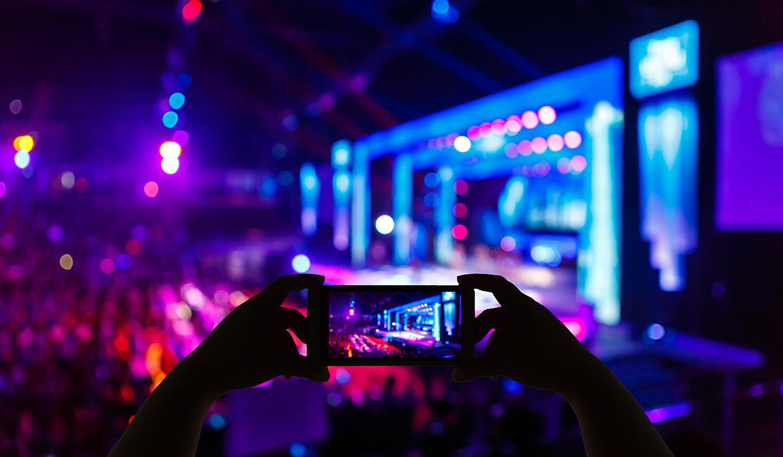 Une jeune femme qui prend une photo avec son smartphone lors d'une conférence d'entreprise