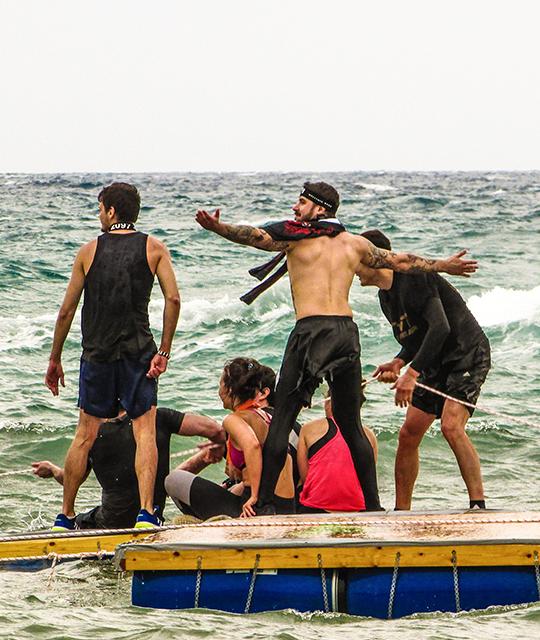 Des salariés d'une entreprise qui s'amuse sur un ponton au bord d'une plage pour organiser un stage de survie d'entreprise