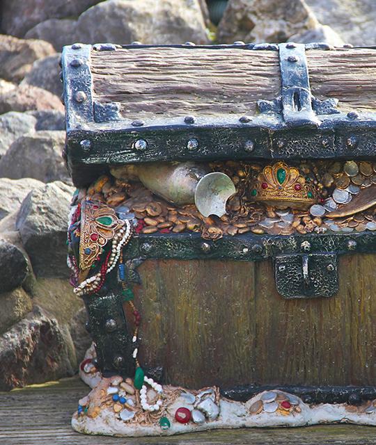 Coffre en bois ouvert avec de l'or pour organiser une chasse aux trésors d'entreprise sur une plage