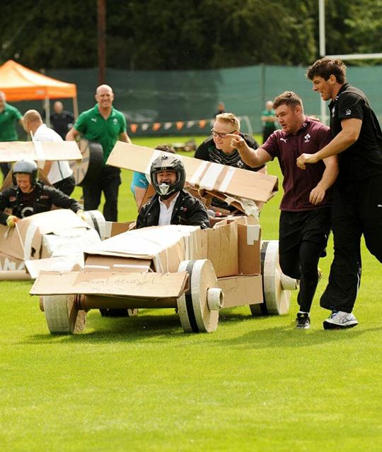 Groupe de salariés qui participe à une course de voiture en carton